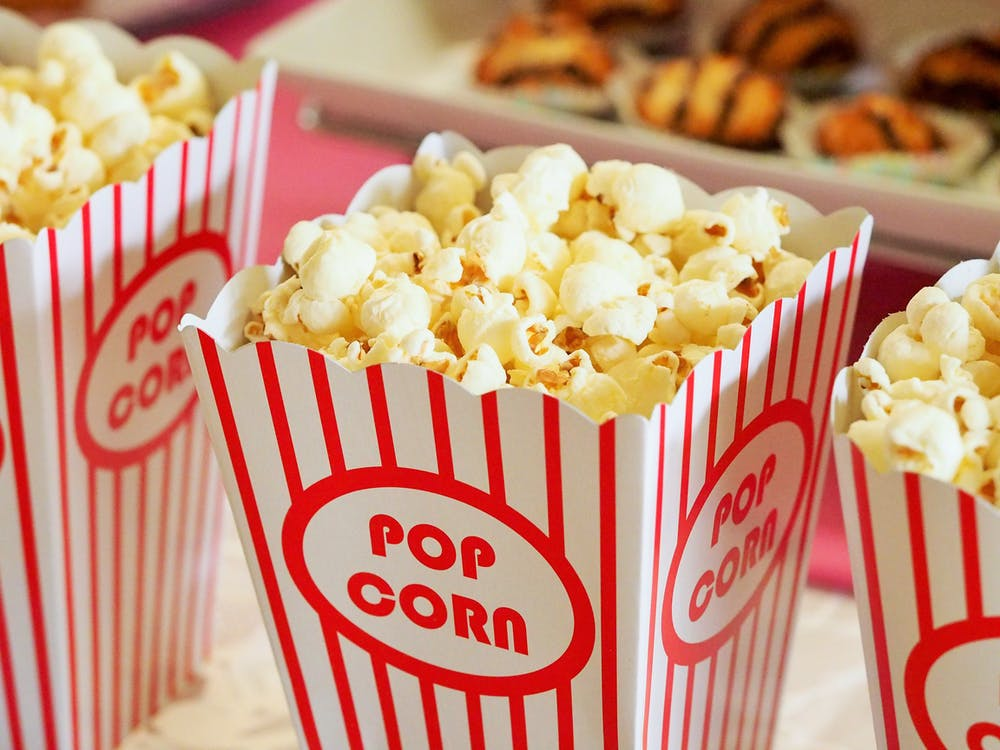 red and white movie popcorn container filled with popcorn