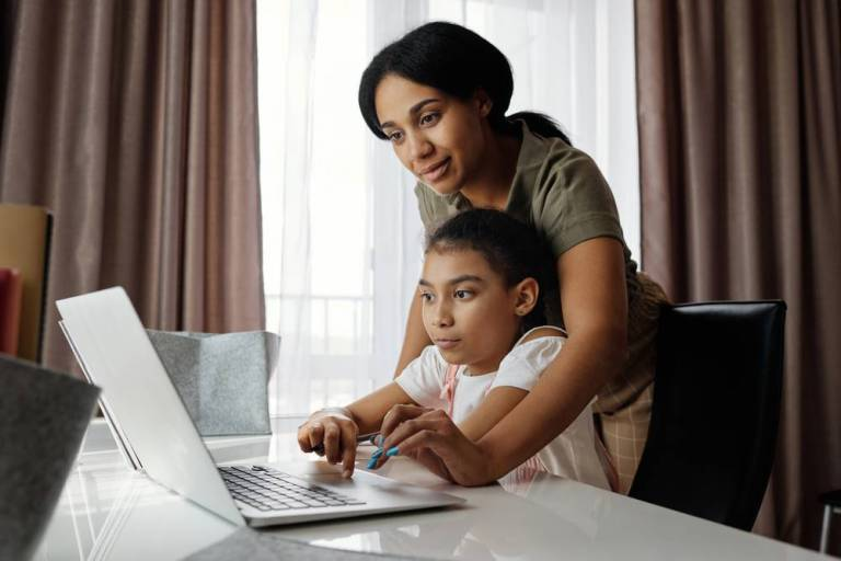 homeschooling, woman standing behind girl sitting at computer