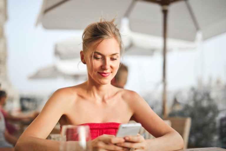 swimming pool safety, woman using phone at umbrella table
