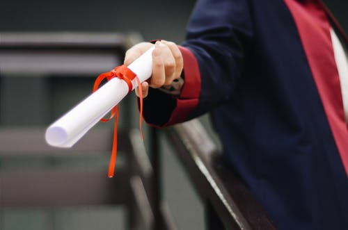 hand holding diploma wrapped in red ribbon