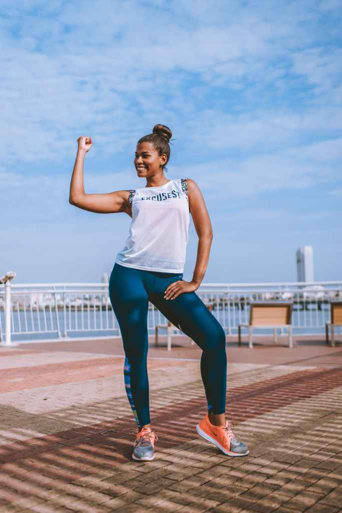 body shaming, woman in blue leggings standing on boardwalk, smiling