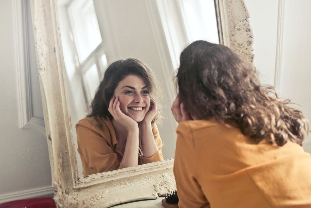 woman leaning face in hands and smiling in mirror