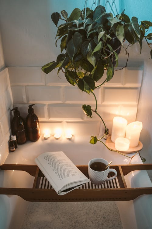 book and cup of coffee on tray over bathtub, candles, plant, soap pumps