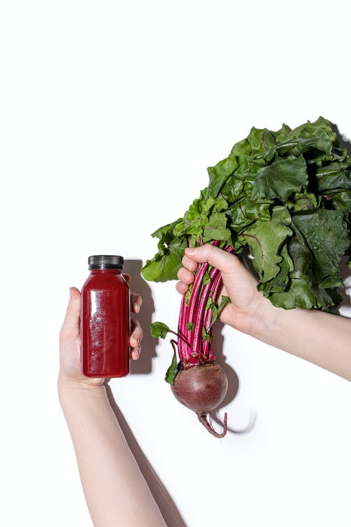 hands holding beets and a jar of beet juice