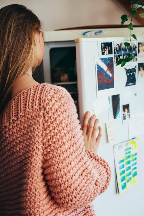 girl in pink sweater with hand on refrigerator door, looking inside fridge