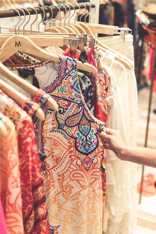 hand holding onto print dress on a hanger