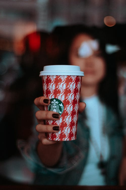girl with dark painted nails holding out green and red starbucks cup with white lid