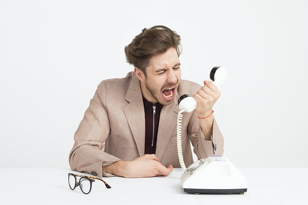 man in beige suitcoat yelling into phone