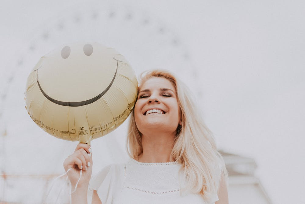 live a happier life, woman smiling and holding smiley face balloon