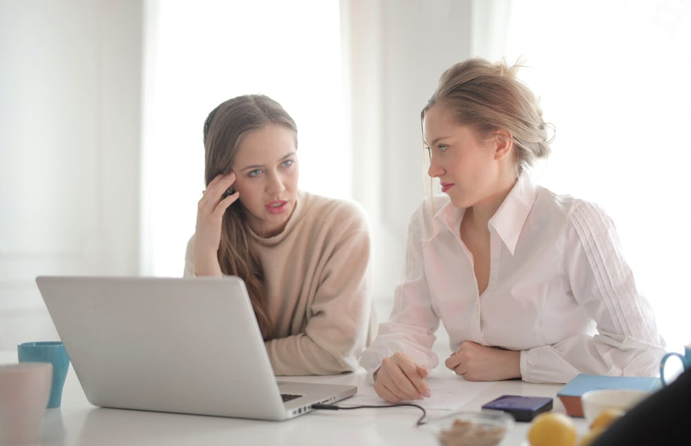 workplace, two women at computer desk