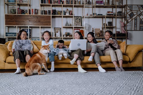 Asian family, laughing, sitting on couch, dog nearby