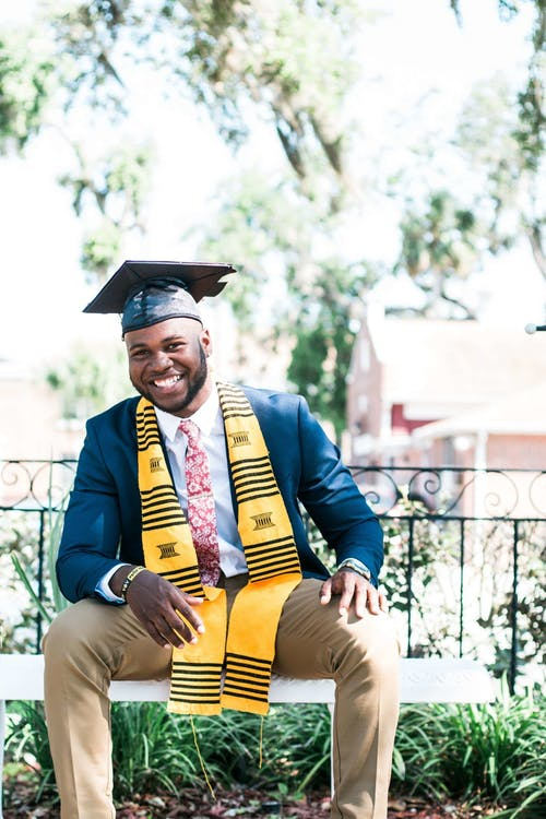 black man with beard, smiling, sitting, wearing college graduation stole, cap and gown