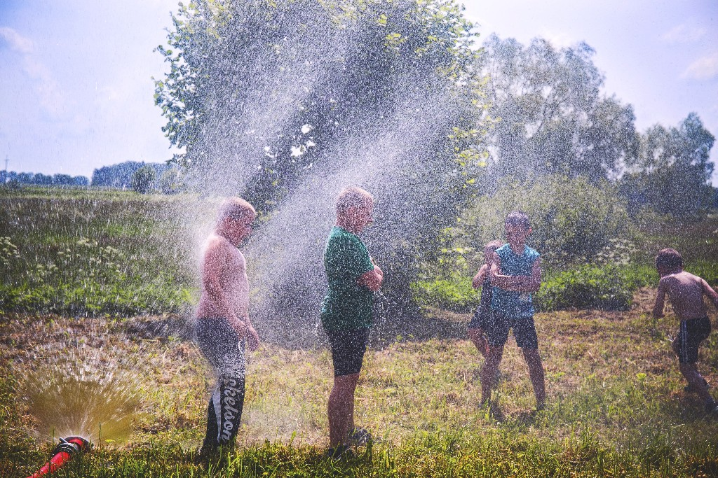 Children playing in sprinkler water