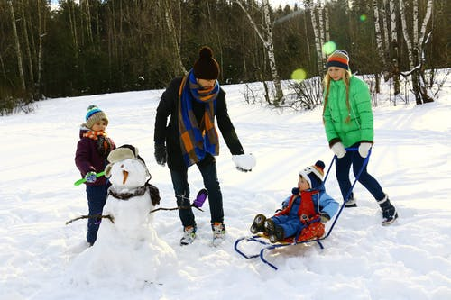 snow, child on sled, child building snowman, man in scarf and hat, woman in green coat pushing sled