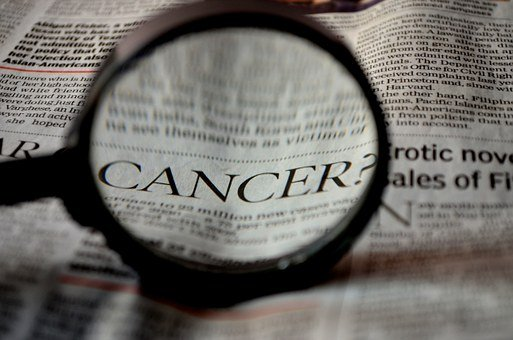 "magnifying glass showing the word ""cancer"" on newspaper"