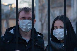 wearing masks, man and woman behind iron bars