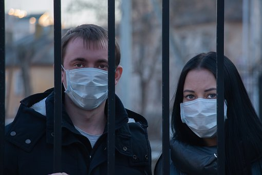 wearing masks, man and woman behind iron bars