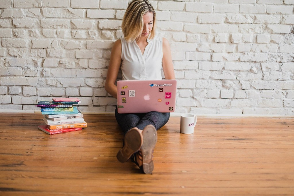 girl with blone hair sitting on floor with pink laptop, pile of books, coffee cup