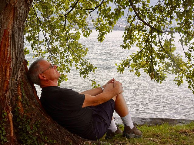 habits in life, man in black tee shirt and shorts, wearing glasses, sitting up against tree with hands wrapped around knees, boy of water in background