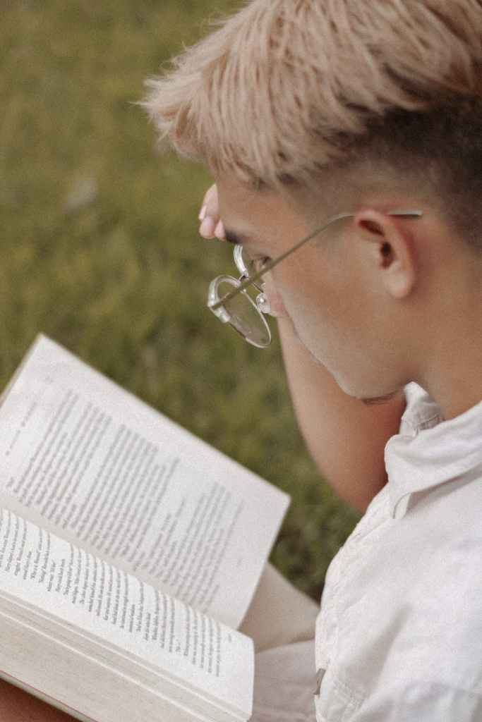 habits in life, blond-haired man with wire rim glasses, reading a book