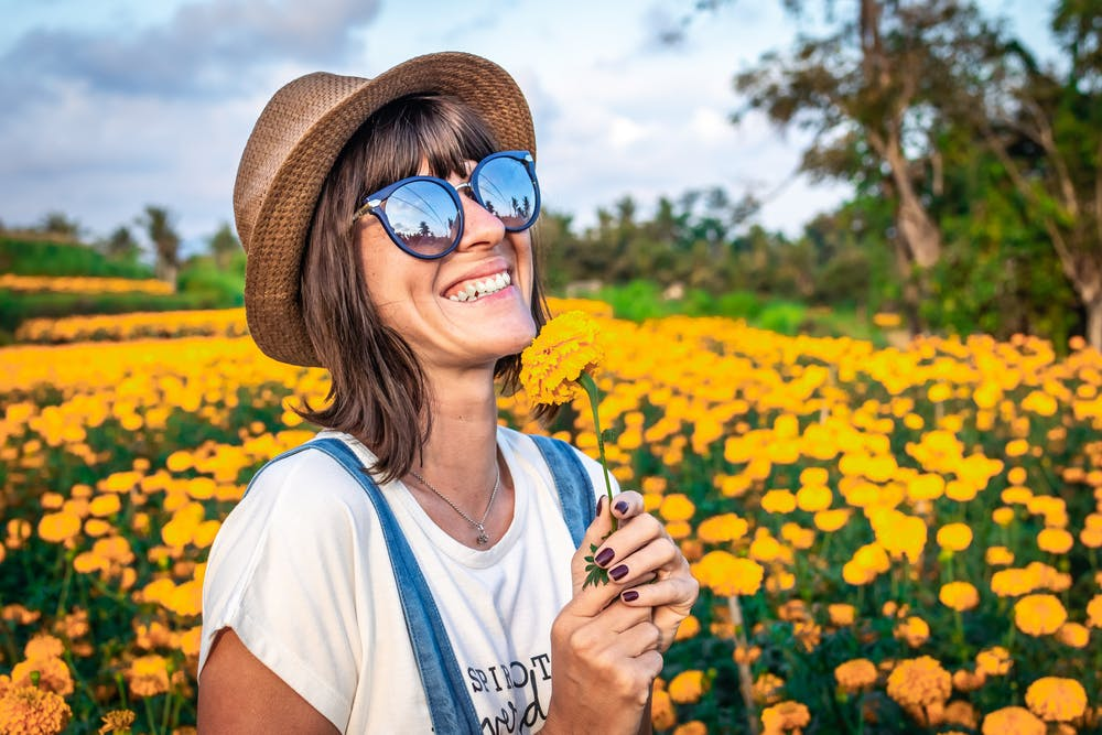 woman in sunglasses, hat, overalls, white tee, smiling and standing in field of flowers