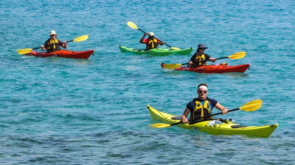 kayaking, group of people in red, yellow and green kayaks on water