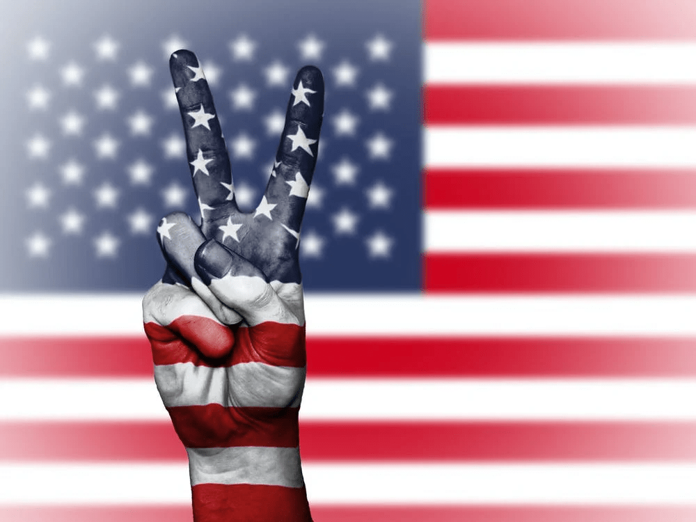 American flag, fingers showing peace sign, painted red, white and blue