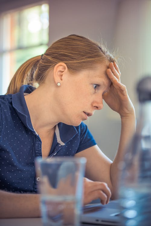homeschooling ideas, woman with ponytail, blue shirt, head in hand, glass of water on desk