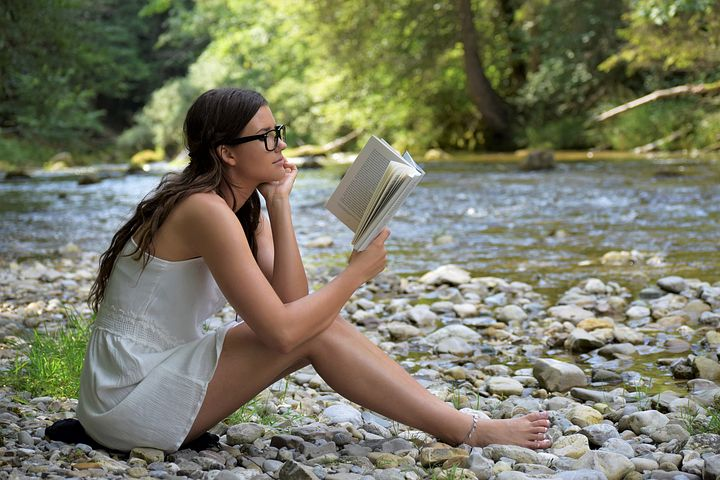 spending time alone, woman with long brown hair and glasses, sitting by creek, reading book, white dress