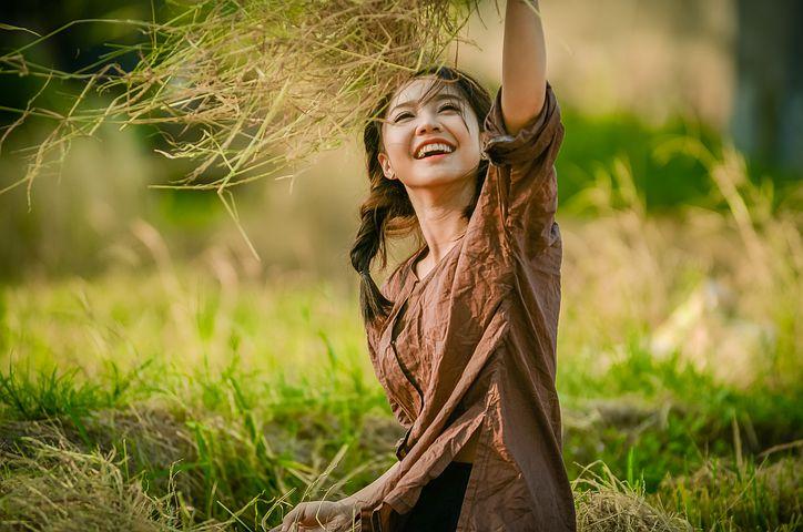 Asian woman sitting in grass, reaching up