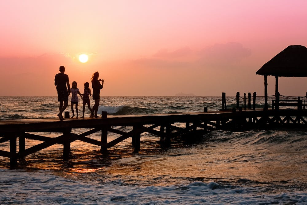 man, woman, two kids standing on pier, sun rising high in background, rough water