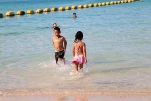 ocean safety tips, children in knee-deep water near shore, yellow swim rope across water