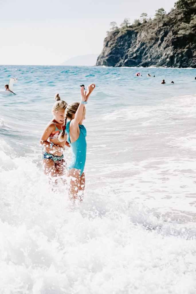 ocean safety tips, two girls splashing in waves, blue bathing suit
