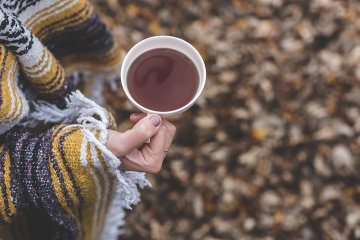 pine needles, fringe of poncho, hand holding cup of tea