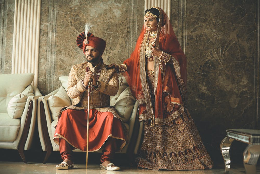 wedding customs, man and woman in elaborate red and gold clothing