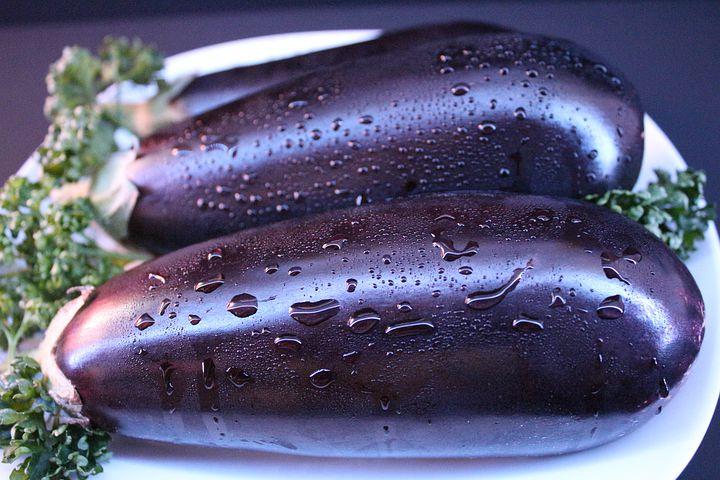 eggplant, two dark purple eggplants, water droplets on skin