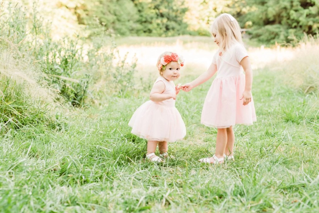 Sister's in their matching pink tulle dresses at a golden hour outdoor photo shoot.