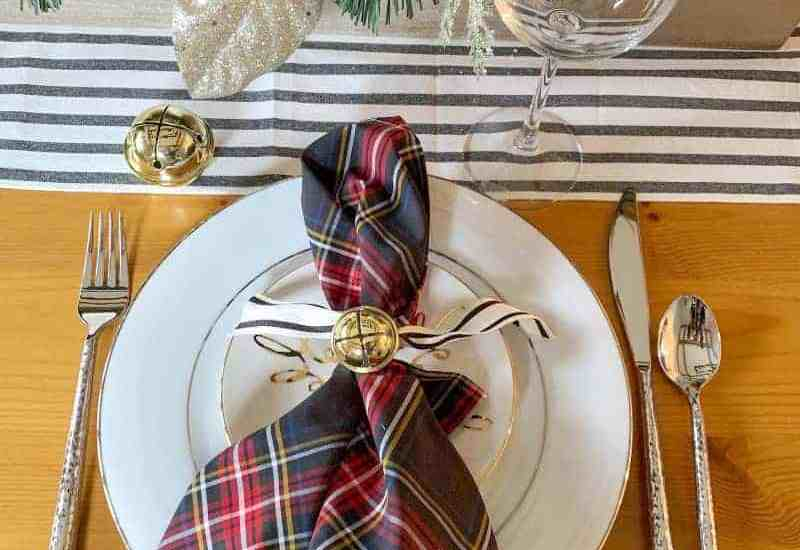 preppy holiday table setting with plaid napkins and striped runner
