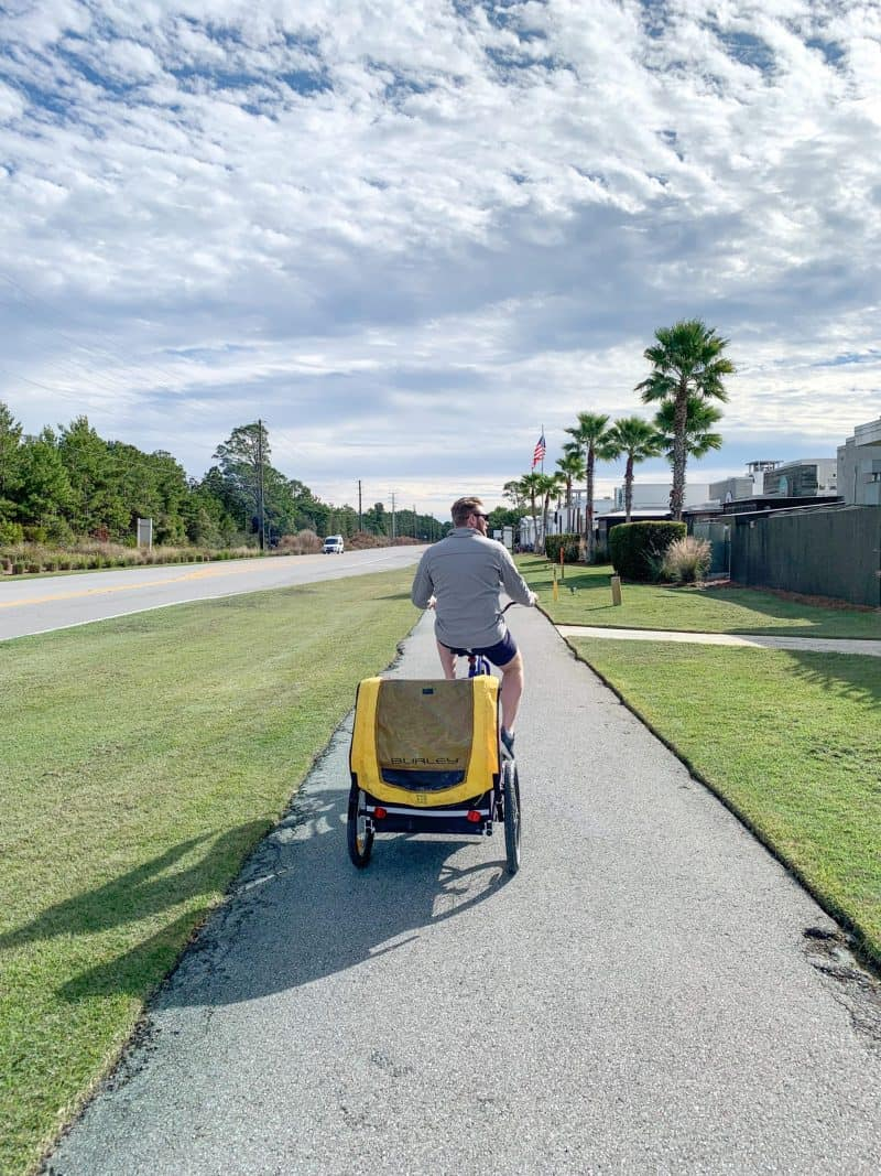 The Ultimate 30A Travel Guide for Families featured by top US travel blog, House of Navy: image of dad biking with buggy on the back