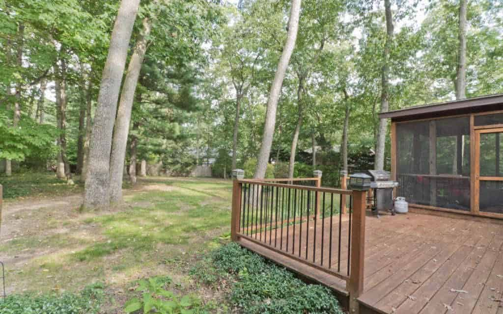 Home Buying with MSHDA info featured by top Michigan lifestyle blog, House of Navy: image of a wooded backyard home