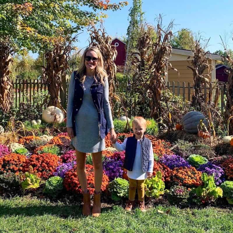 mother and son in front of pumpkins | Living in Michigan by popular Michigan lifestyle blog, The House of Navy: image of a mom and her son standing near some pumpkins at the Frederik Meijer Gardens in Grand Rapids, MI.