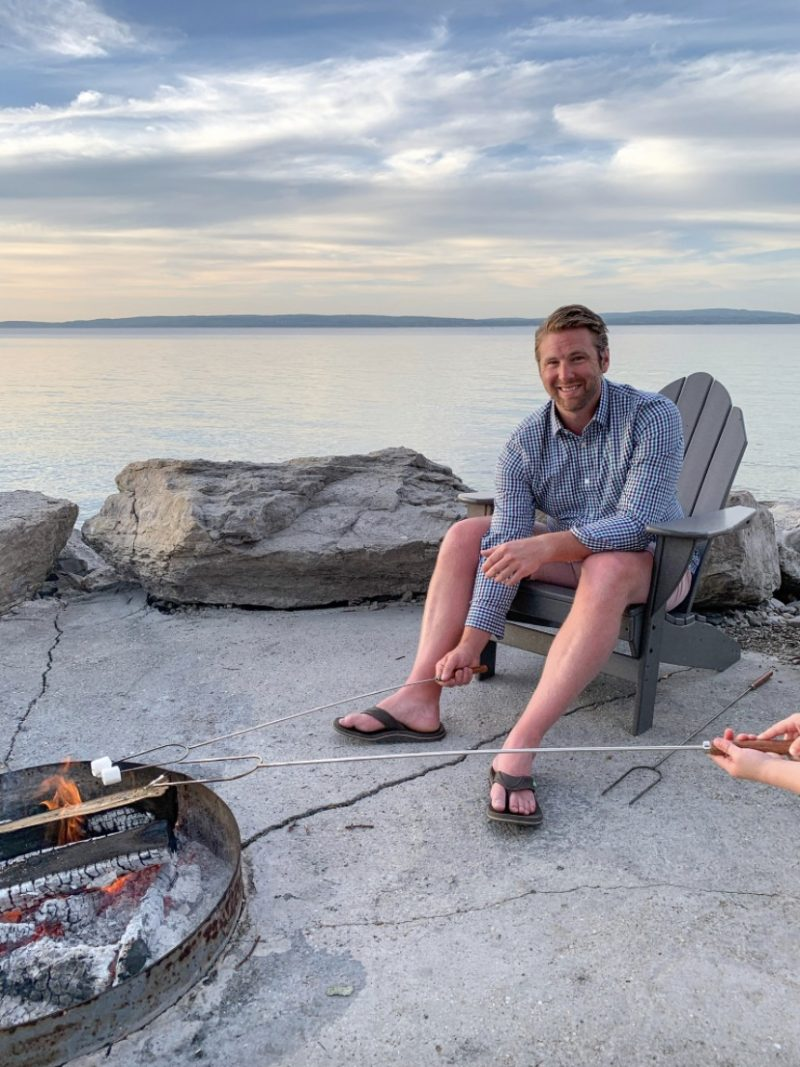 man roasting marshmallow | Living in Michigan by popular Michigan lifestyle blog, The House of Navy: image of a man roasting marshmallows in Petoskey, MI.