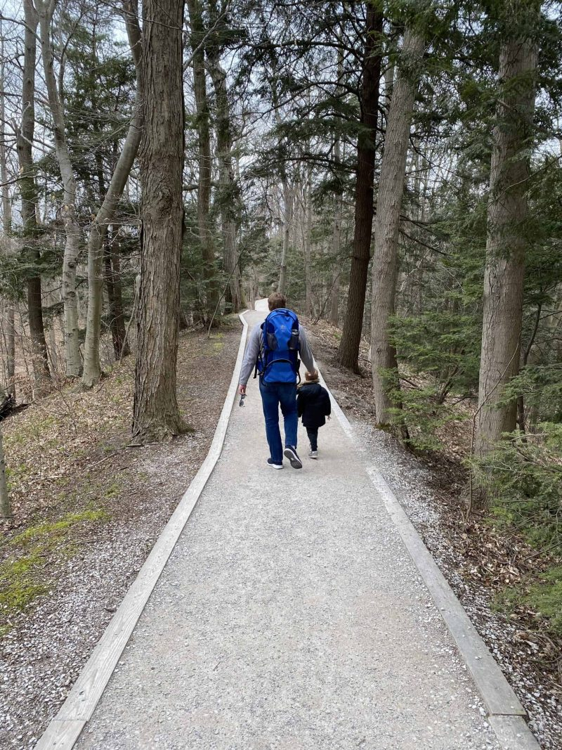 father and son hiking | Living in Michigan by popular Michigan lifestyle blog, The House of Navy: image of a father and son hiking in Grand Haven, MI.