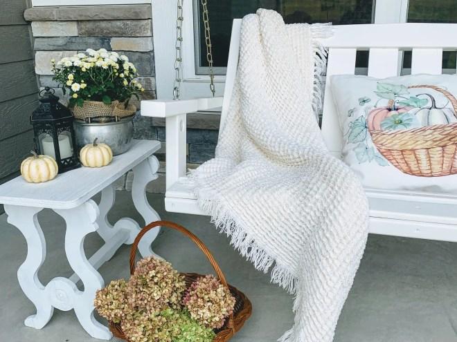 A porch swing, a cozy blanket, pumpkins, mums. lanterns, and dried hydrangeas