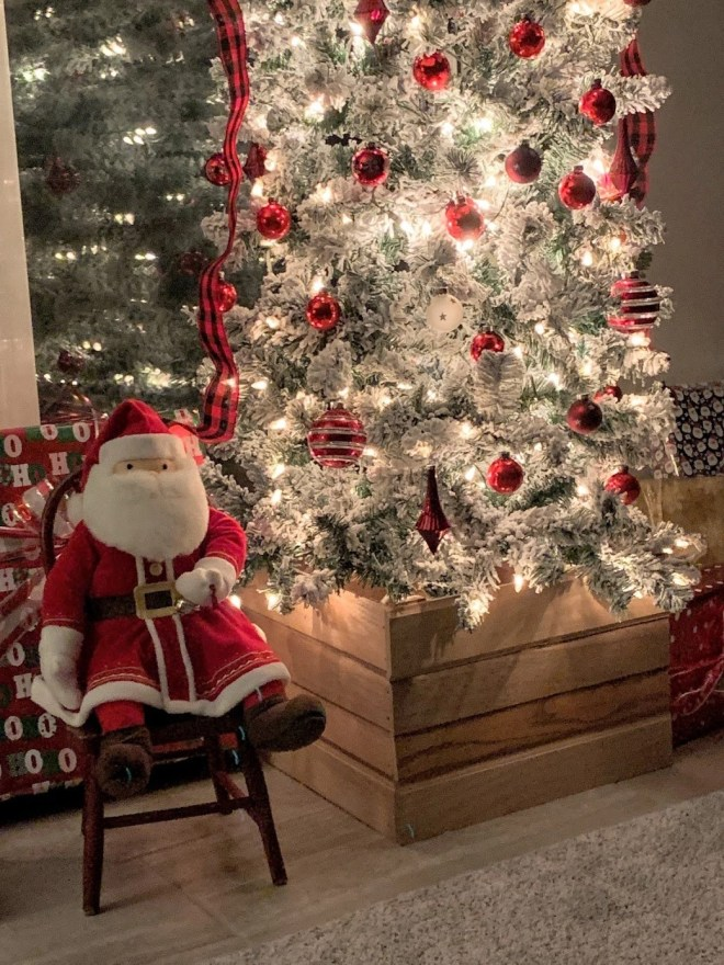 DIY Christmas Tree Box Stand, vintage red Christms Bulbs, Santa and antique child's chair complete the farmhouse look.