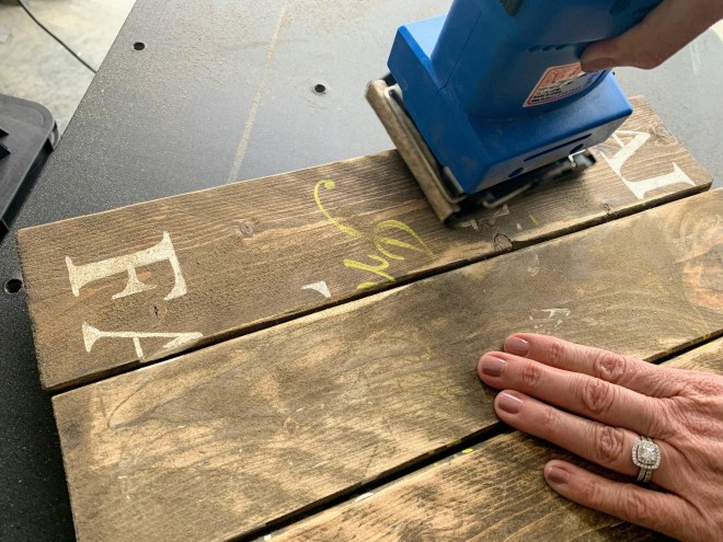 Sanding the signs to remove old wording for my DIY Thrift Store Farmhouse Sign Makeover