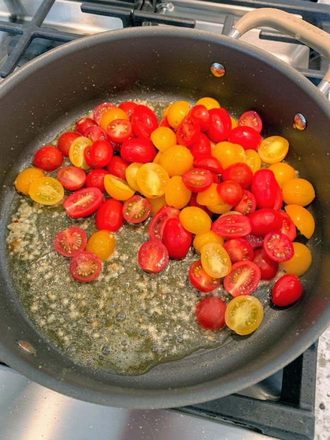Adding the tomatoes to the Garlic Butter & Tomato Pasta