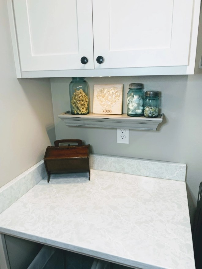 Shelf to keep clutter off counters in laundry space.