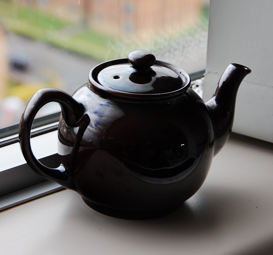 A black teapot on a windowsill