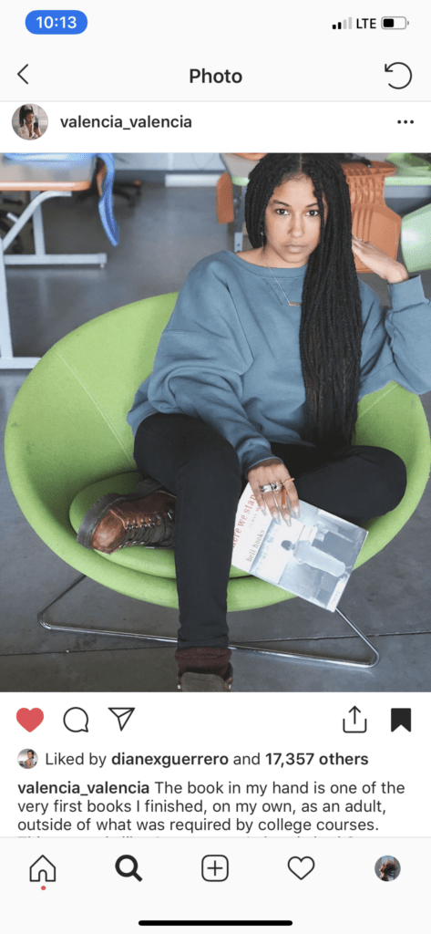 Screenshot of Valencia De'La Clay on Instgram sitting in a green chair with a book in her hand.